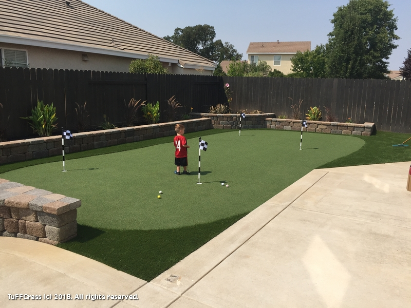 ... A Large Artificial Grass Lawn, Beautiful Paver Patio With Sitting Wall  For Everyone Who Is Enjoying Playing On The Synthetic Turf Putting Green.